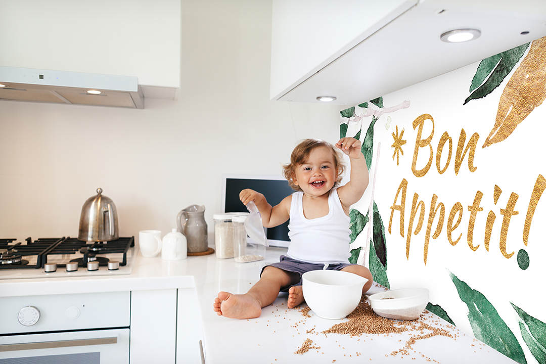 1,4 years old child playing with food ingredients and utensils alone in the white kitchen table